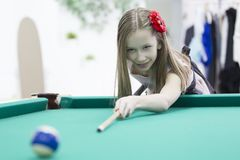 Little girl playing pool royalty free stock images