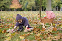 Little girl playing with a pram in the park Stock Photos