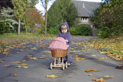 Little girl playing with a pram in a park Stock Photo