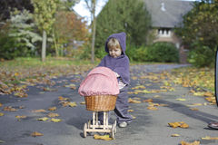 Little girl playing with a pram in a park Stock Images