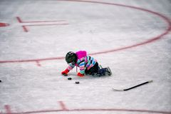 Little girl playing with pucks in hockey rink. A five year old girl in winter gear and hockey helmet and skates lining up a row of pucks on an ice skating rink Royalty Free Stock Photos