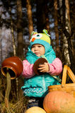 Little girl playing with pumpkins on autumn nature Stock Photo