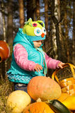 Little girl playing with pumpkins Royalty Free Stock Images