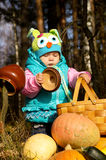 Little girl playing with pumpkins on the nature Royalty Free Stock Images