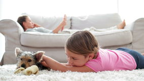 Little girl playing with puppy chewing bone with her mother reading on the sofa