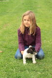 Little girl playing with a puppy. Kneeing little girl in violet pullover and blue pants playing with a black and white puppies Stock Image