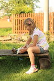 Little girl playing with a puppy. Little girl in pink and white t-shirt and blue shorts playing with a brown and white puppy on a wooden seat Royalty Free Stock Photo