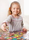 Little girl playing puzzle Stock Images