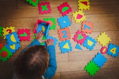 Little girl playing with puzzle, early education. Concept stock images