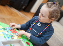 Little girl playing puzzle game Stock Images