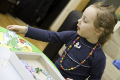 Little girl playing a puzzle game Royalty Free Stock Image