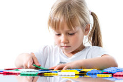 Little girl playing with puzzle pieces. Stock Images