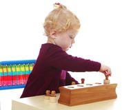 Little girl playing puzzle sitting at the table Royalty Free Stock Photo