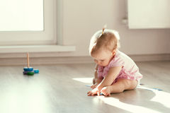 Little girl playing with pyramid on floor Royalty Free Stock Photo