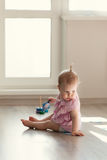 Little girl playing with pyramid on floor Stock Photo