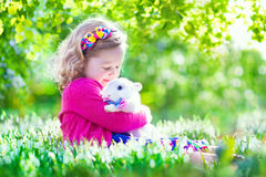 Little girl playing with a rabbit Stock Photos