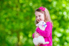 Little girl playing with rabbit Stock Photo