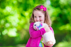 Little girl playing with rabbit Royalty Free Stock Photo