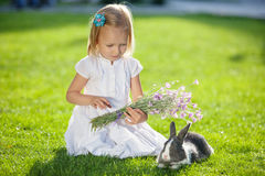 Little girl playing with rabbit Stock Images