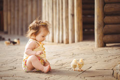 Little girl playing with rabbit in the village. Outdoor. Summer portrait. Royalty Free Stock Photography