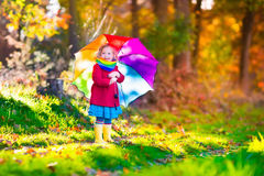 Little girl playing in the rain in autumn. Park. Child holding umbrella walking in the forest on a sunny fall day. Children playing outdoors with yellow maple Royalty Free Stock Photo