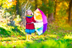 Little girl playing in the rain in autumn. Park. Child holding umbrella walking in the forest on a sunny fall day. Children playing outdoors with yellow maple Royalty Free Stock Image