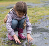 Little girl playing in the rain Royalty Free Stock Image