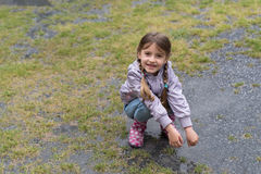 Little girl playing in the rain Stock Image