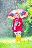 Little girl playing in the rain. Funny cute curly toddler girl wearing red waterproof coat and yellow rubber boots holding colorful umbrella playing in the Stock Photography