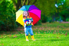 Little girl playing in the rain holding colorful umbrella. Child with colorful umbrella playing in the rain. Kids play outdoors by rainy weather. Toddler kid in Stock Photo