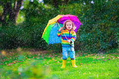 Little girl playing in the rain holding colorful umbrella Stock Photos