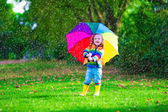 Little girl playing in the rain holding colorful umbrella stock image