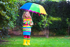 Little girl playing in the rain under colorful umbrella. Little girl with colorful umbrella playing in the rain. Kids play outdoors by rainy weather in fall Stock Images