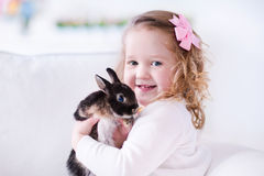 Little girl playing with a real pet rabbit. Child playing with a real rabbit. Kids play with pets. Little girl holding bunny. Children and animals at home or Stock Image
