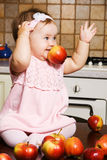 Little girl playing with red apples Royalty Free Stock Photo