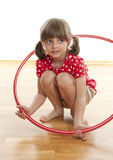 Little girl playing with a red hoop Royalty Free Stock Photo