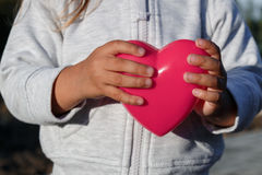 Little girl playing with a red plastic heart. she holds it in her hands Royalty Free Stock Photos