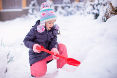 Little girl playing with red shovel in the garden Stock Image