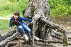 Little girl playing on the roots of a tree. Little restless girl with two plaits plays on the roots of a large tree. Selective focus royalty free stock image