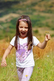 Little girl is playing while running. On green-yellow meadow Royalty Free Stock Photography