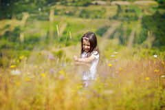 Little girl is playing while running on green-yellow meadow. In untouched nature Royalty Free Stock Photo