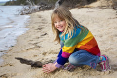 Little girl playing in sand. At the beach stock photo
