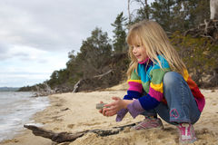 Little girl playing in sand. At the beach royalty free stock image