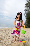 Little girl playing sand. Happy little girl playing sand on beach with bucket and spade Royalty Free Stock Image