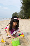 Little girl playing sand. Happy little girl playing sand on beach with bucket and spade Royalty Free Stock Photography