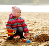 Little girl playing with sand at the autumn beach Royalty Free Stock Photo