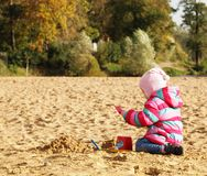 Little girl playing with sand at the autumn beach Royalty Free Stock Photography