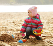 Little girl playing with sand at the autumn beach Stock Image