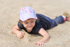 Little girl playing in the sand on the beach. Stock Photos