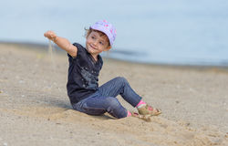 Little girl playing in the sand on the beach. Stock Photo